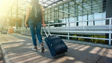 a woman pulls a trolley along the sidewalk on her way to vancouver at abbotsford international airport