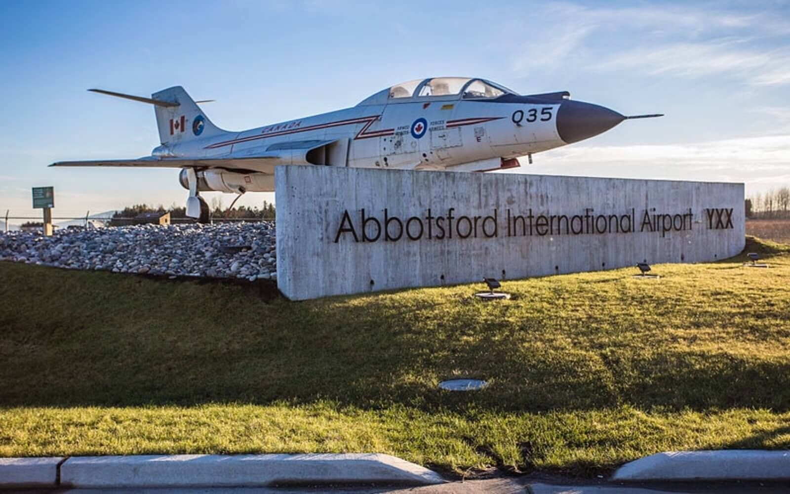 A military jet sits beside the YXX sign