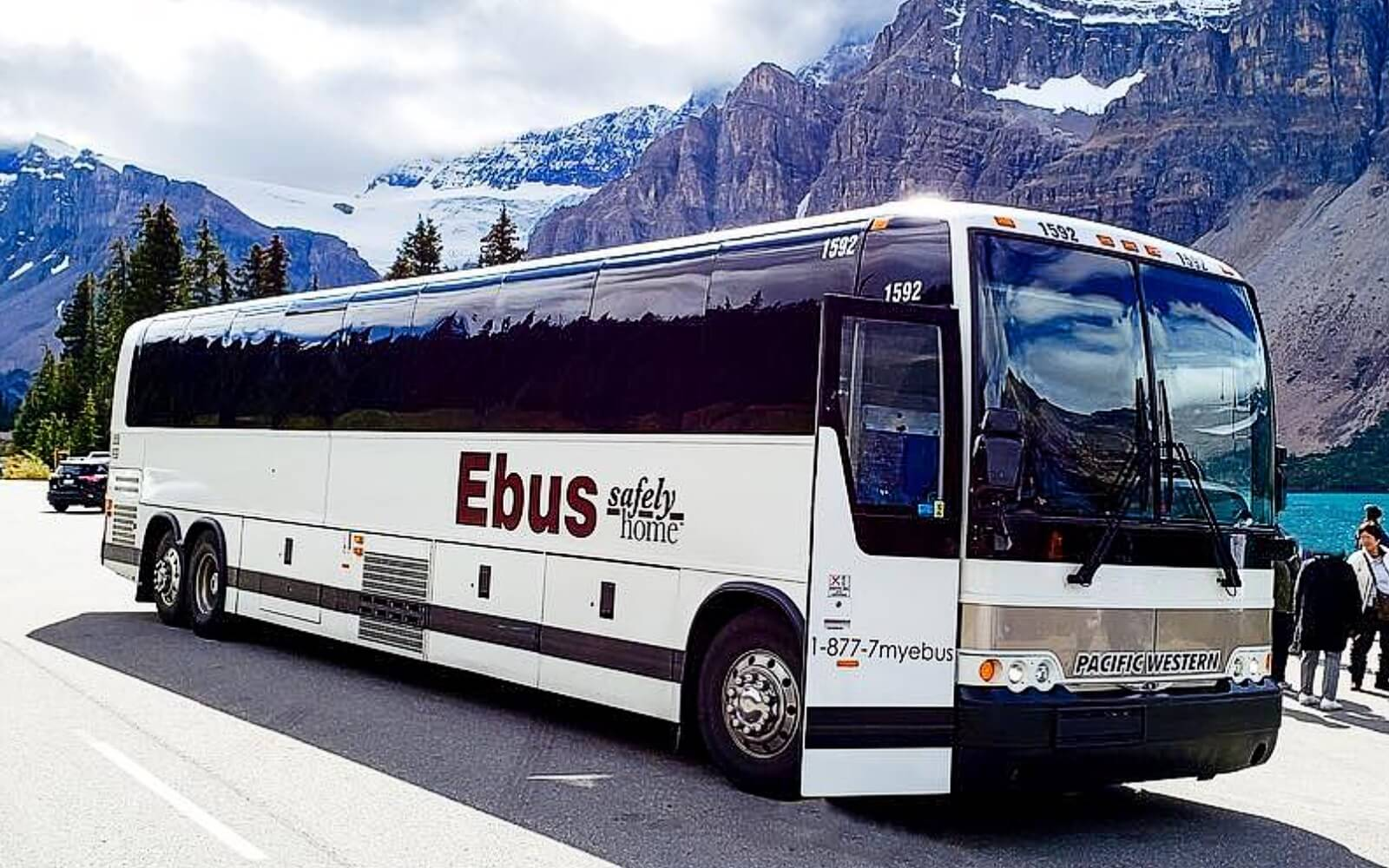 An ebus coach sits in front a of mountain in BC