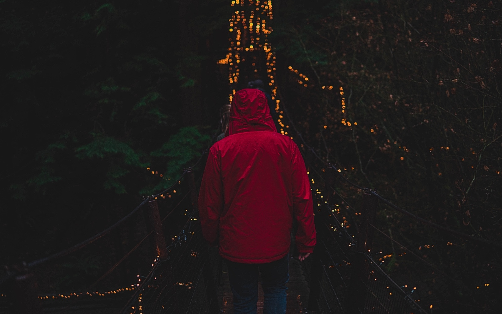 a man in a red jacket crosses the Capilano Suspension Bridge in the evening