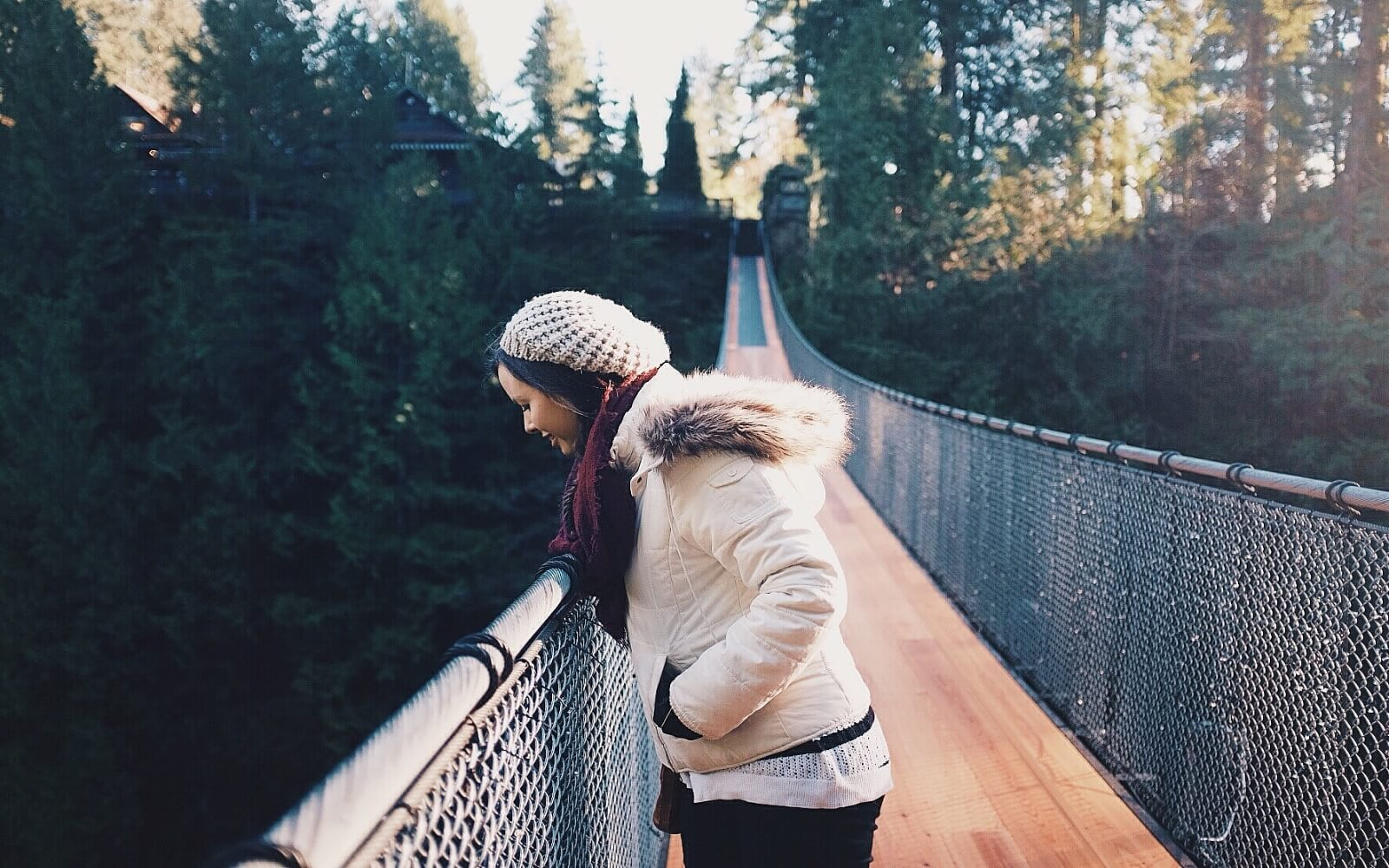 A girl peers over the Capilano Suspension Bridge