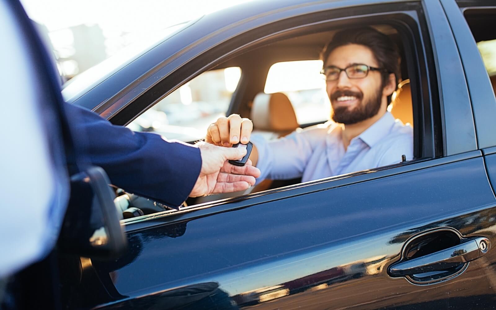 A man receives his rental vehicle