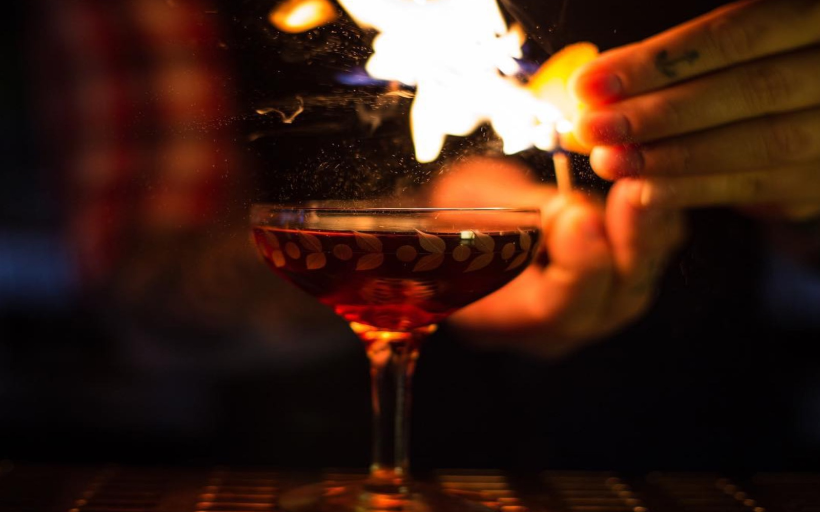Fire alight above cocktail at the Keefer Bar, Vancouver