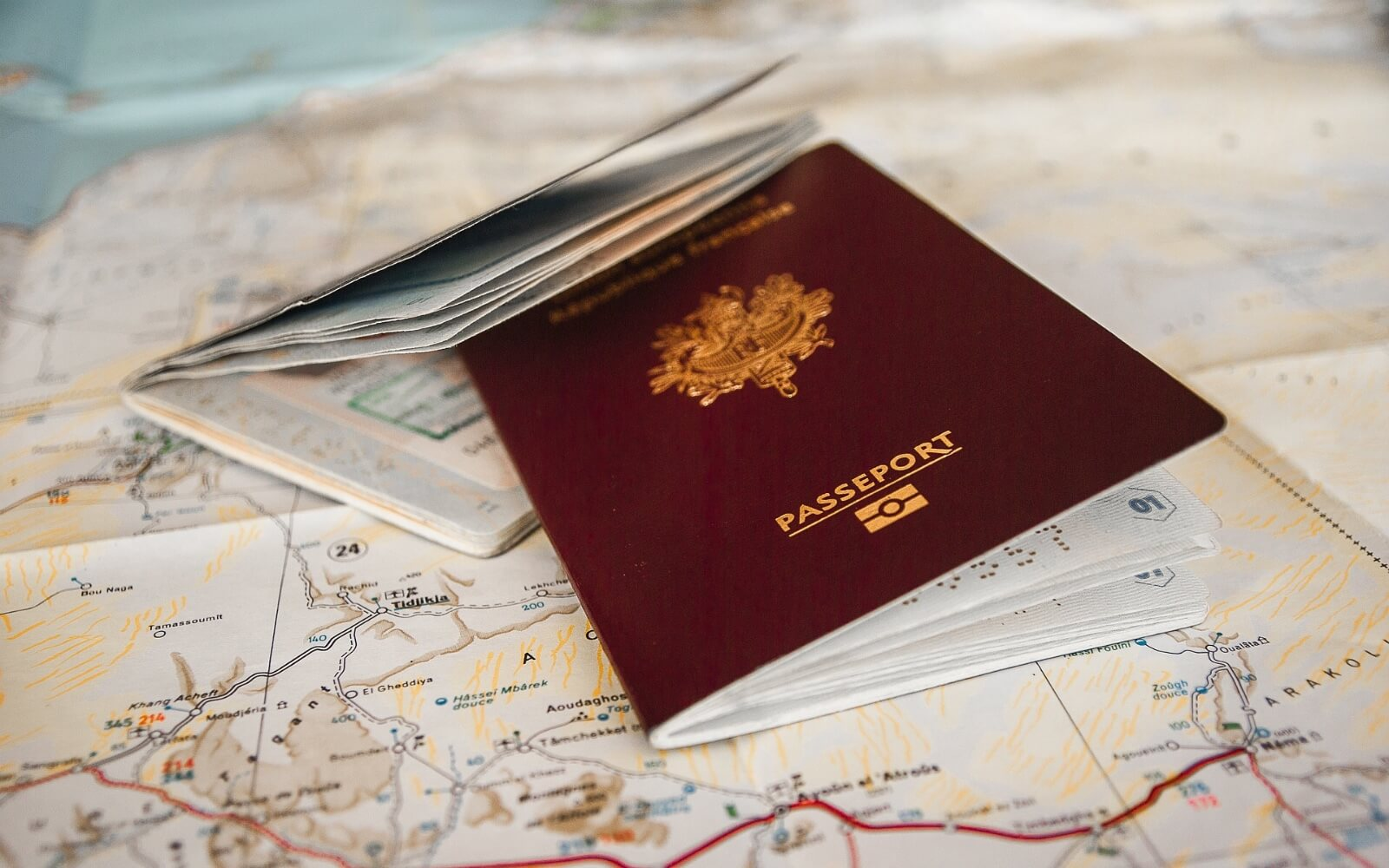 A couple of passports sit on top of a map