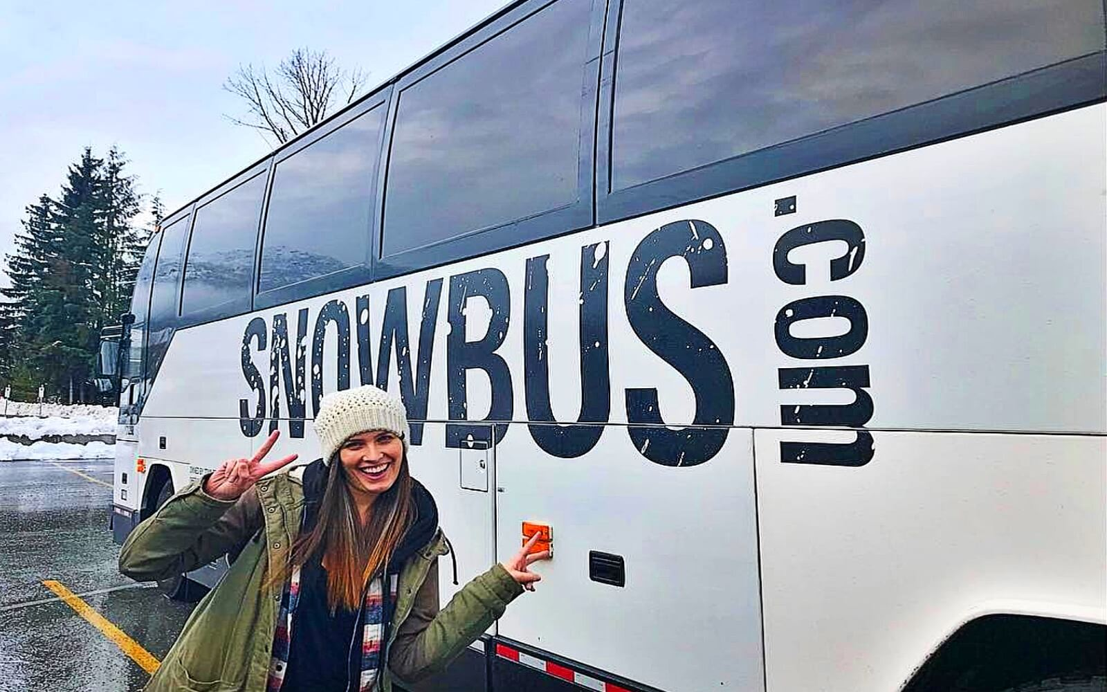 A girl stands in front of the Snowbus shuttle to Whistler