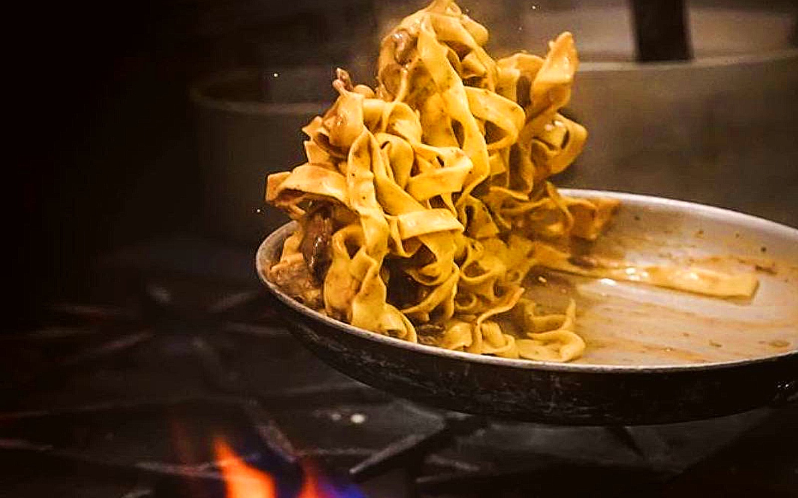 A plate of pasta is flipped in a pan