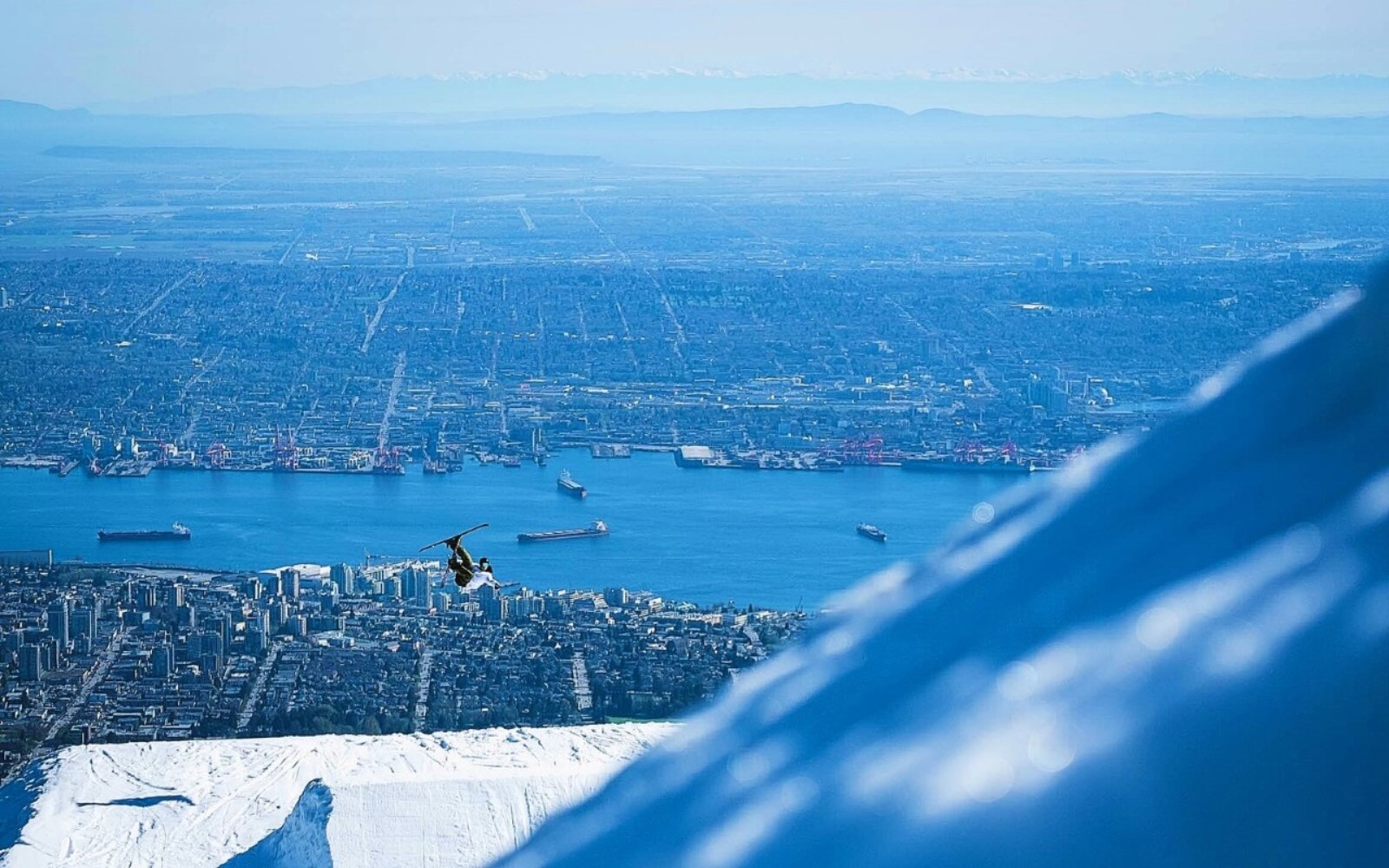A skier jumps on Grouse Mountain in front of the Vancouver skyline