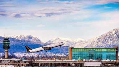 A plane takes off in front of the Fairmont Vancouver Airport
