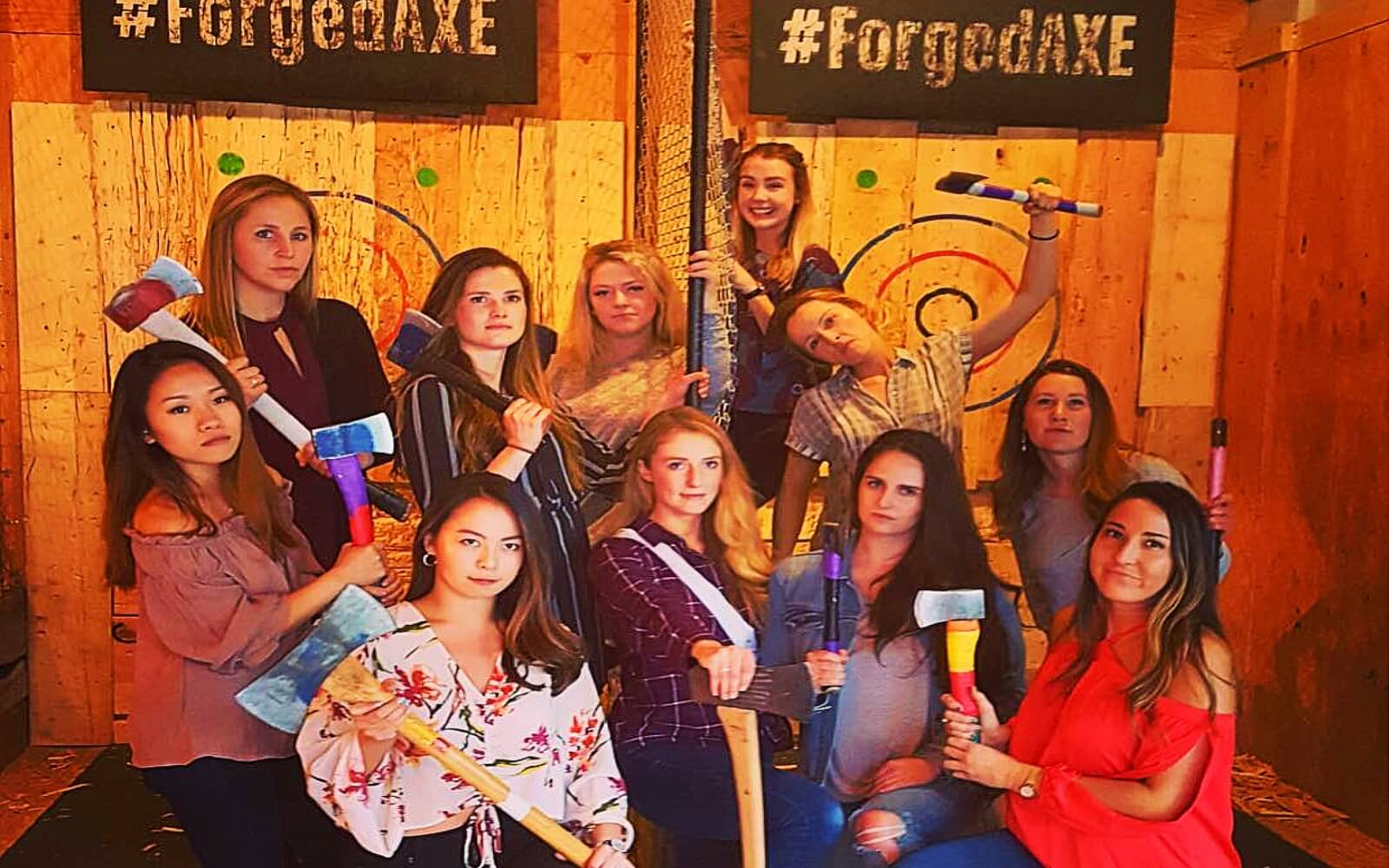 A group of woman pose after a axe throwing contest