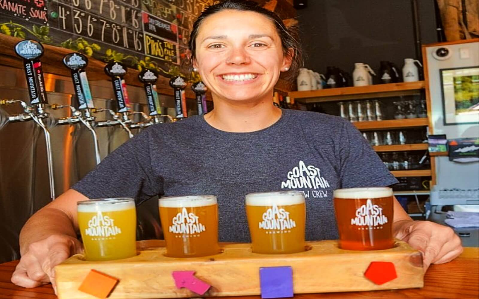 A bartender serves a flight of Coast Mountain beers