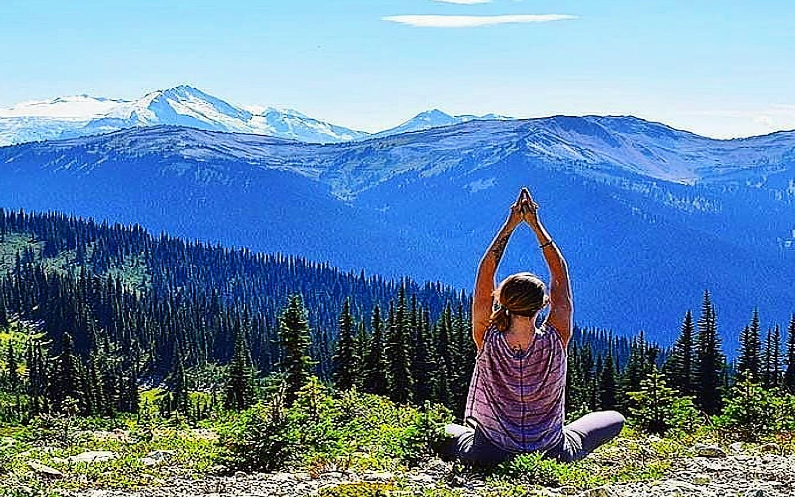A woman does yoga in the mountains