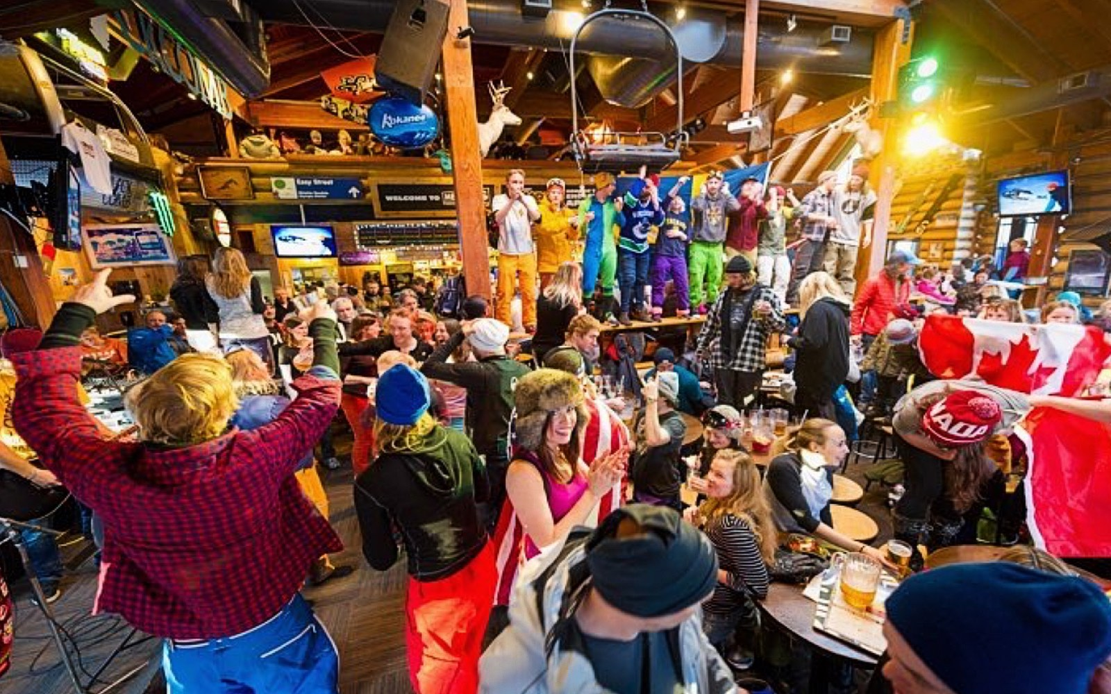 Patrons dance on the table at Merlins, Whistler