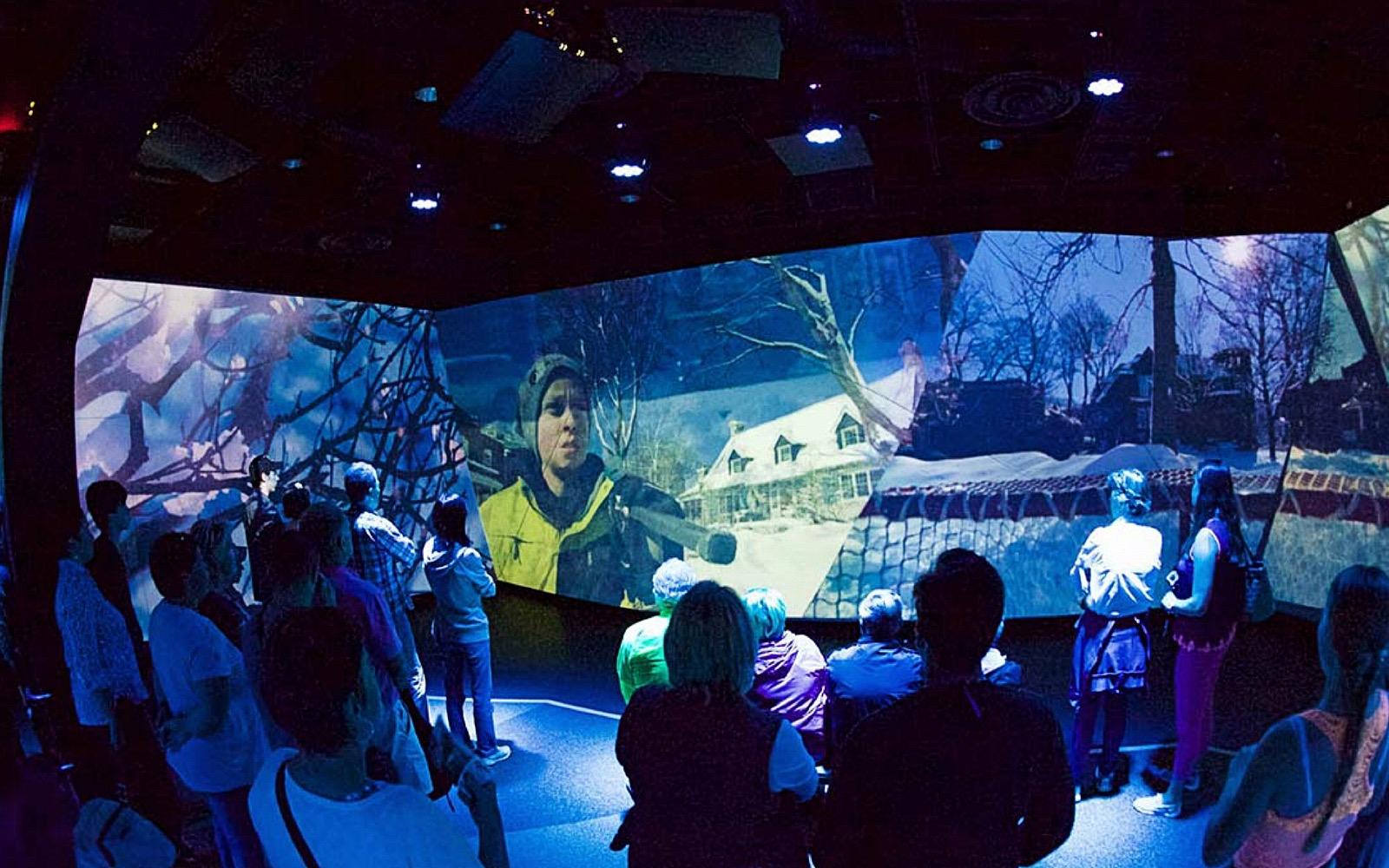 A group walks through the Flyover Canada pre-show exhibit