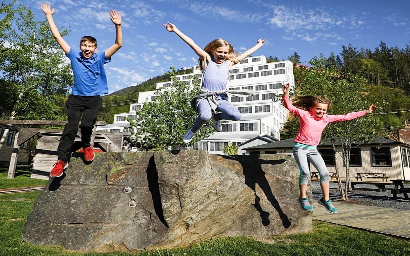 Three children leap in the air in front of the Britannia Mine Museum