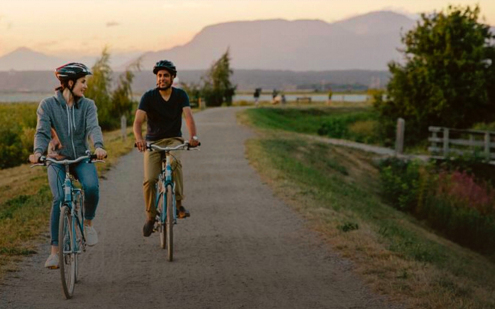 A couple bike along the South Dyke Trail, Steveston BC