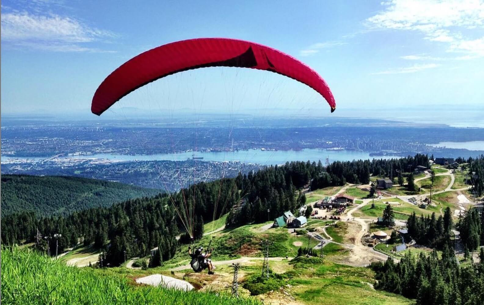 A man paraglides off the peak of Grouse Mountain