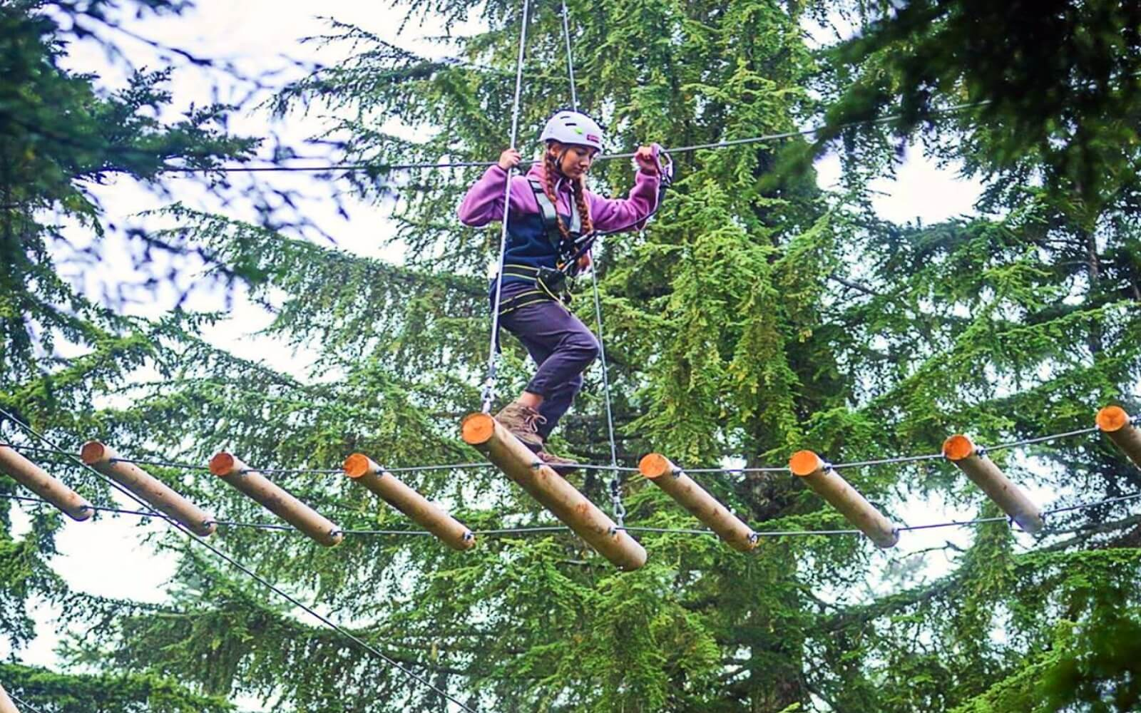 A woman climbs through the forest on a ropes adventure