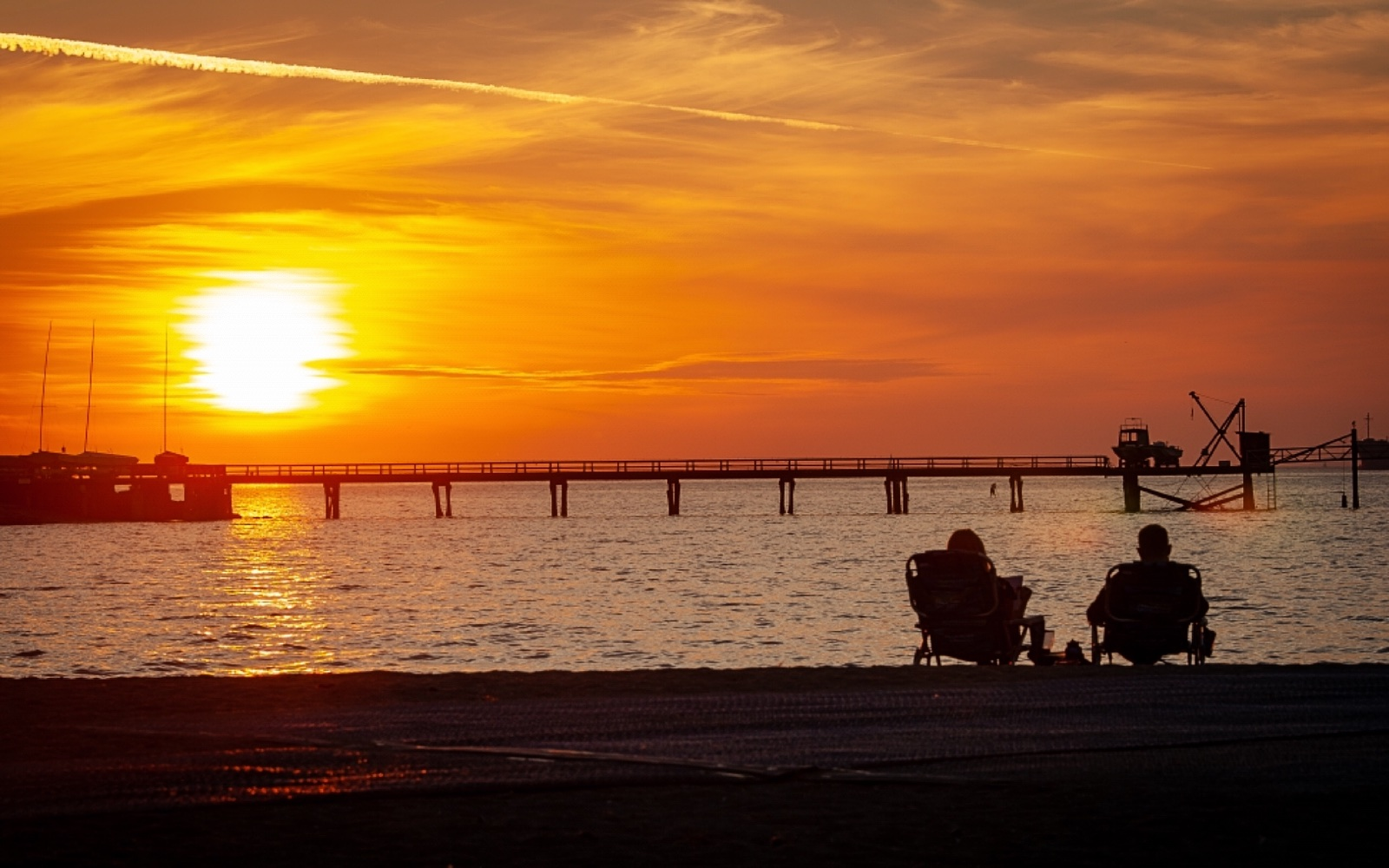 A couple enjoy the sunset on Kitsilano Beach, Vancouver