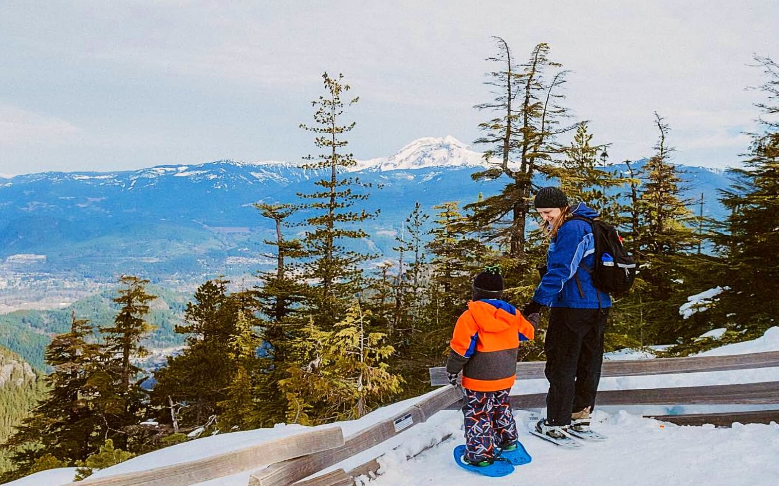 A mother and son snowshoe in the wilderness