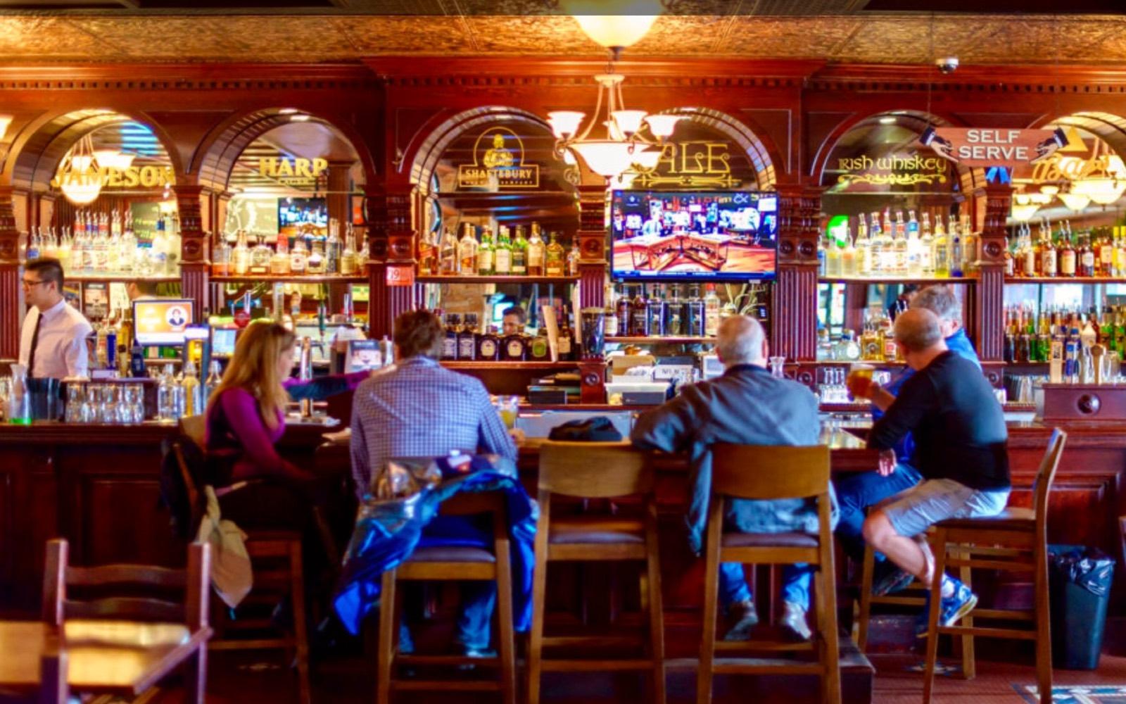 A group sits at the bar at the Buck and Ear, Steveston BC