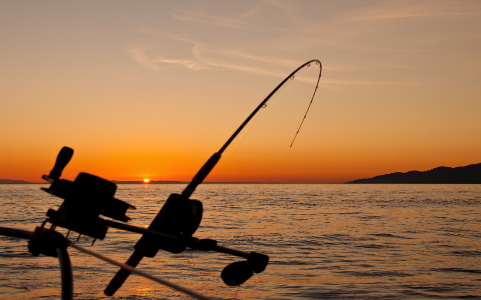 A fishing rod sits in front of a sunset, Salish Sea BC
