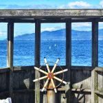 a ship steering wheel looking out into vancouver harbour from Jericho beach