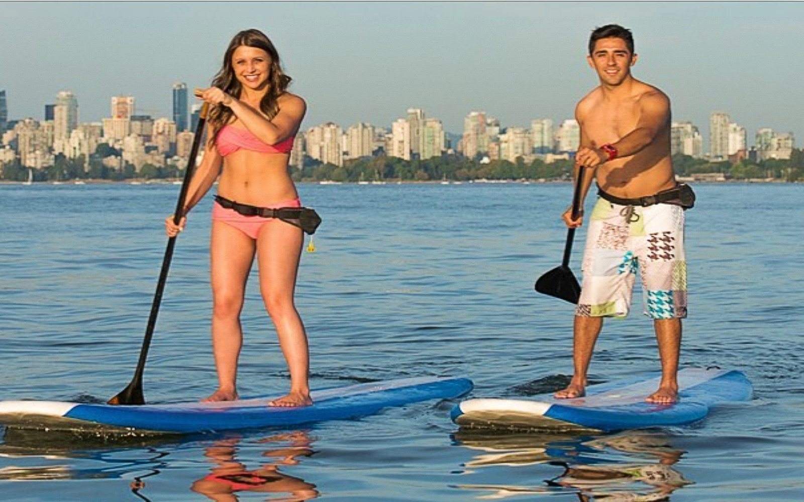 A couple paddle boards in front of the Vancouver skyline
