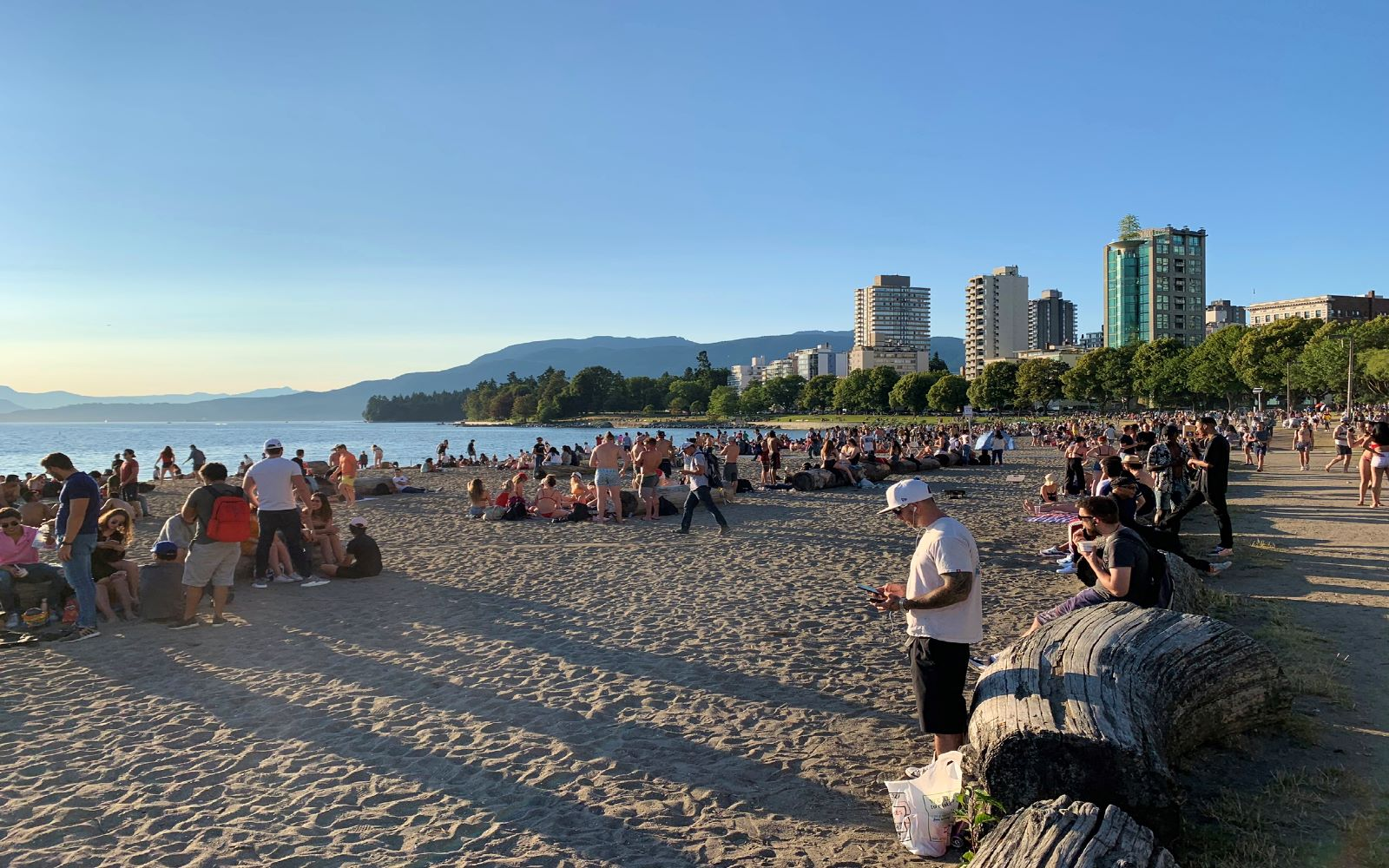 beachgoers watch the sunset from english bay beach in vancouver bc canada