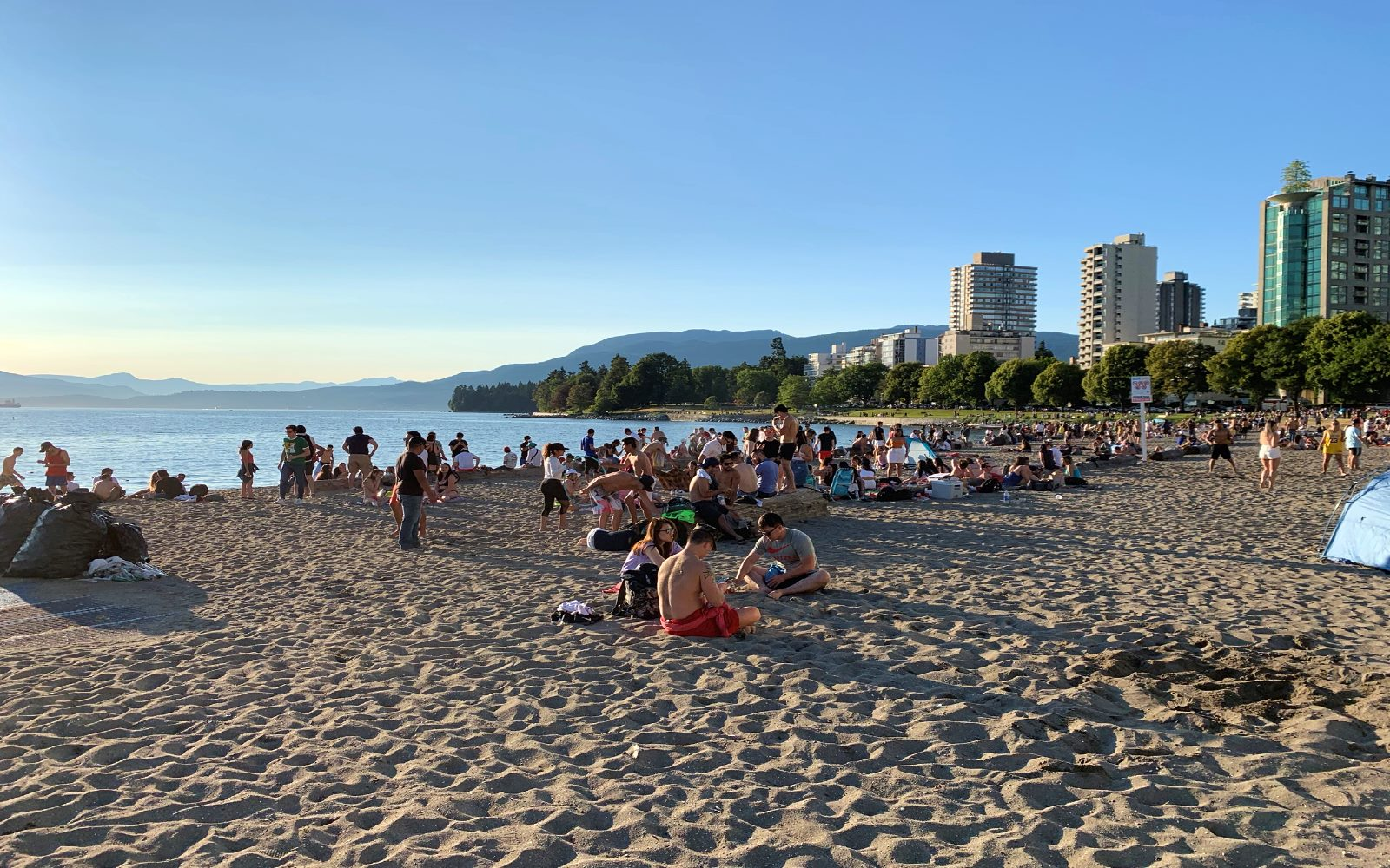 Groups of people enjoy the sunset, English Bay Beach