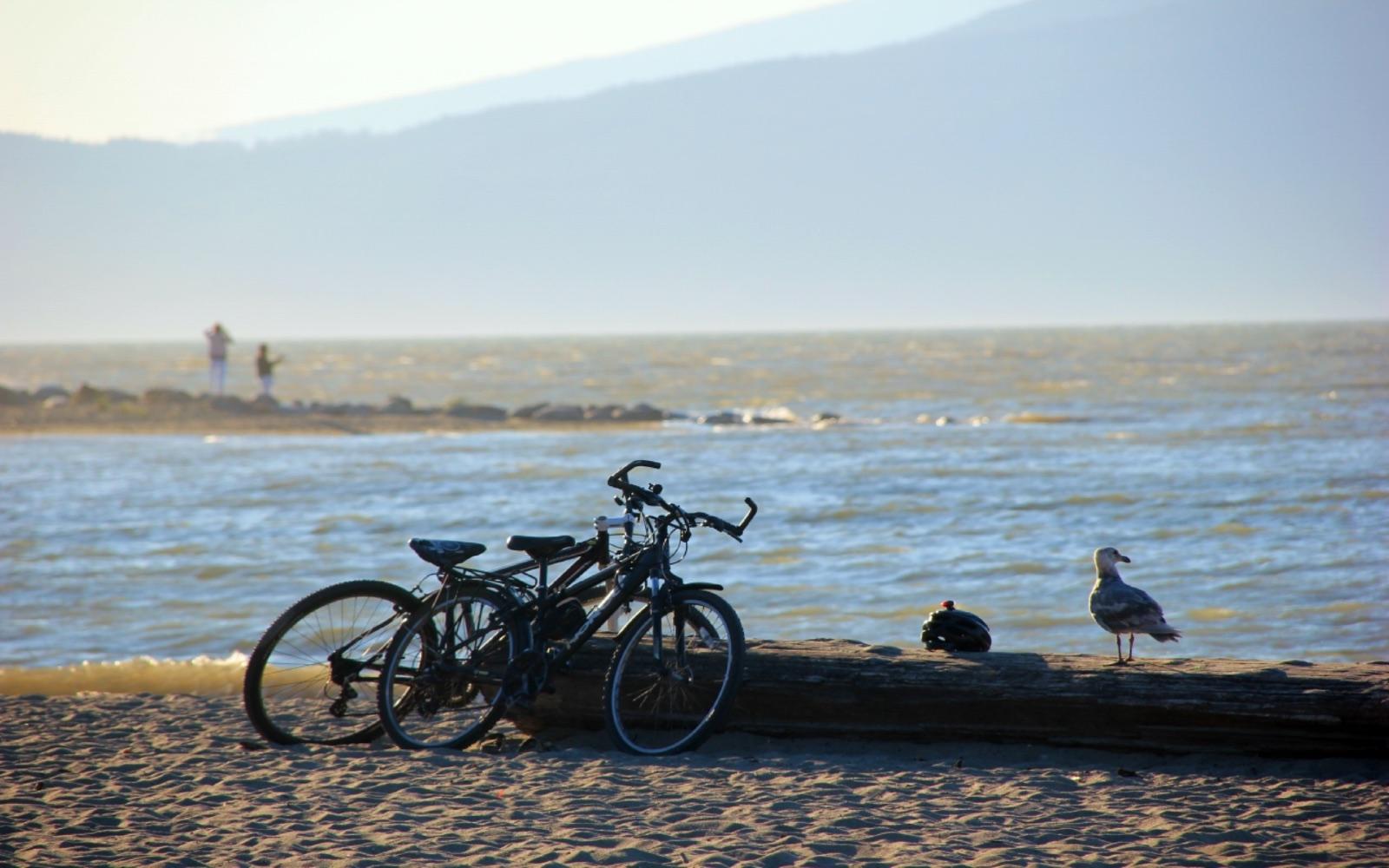 A couple bike to Spanish Banks along the seawall, Vancouver