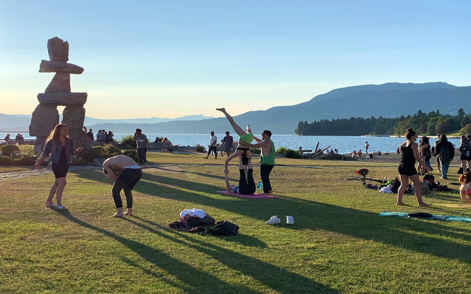 Vancouverites perform yoga in front of the Inukshuk, English Bay Vancouver