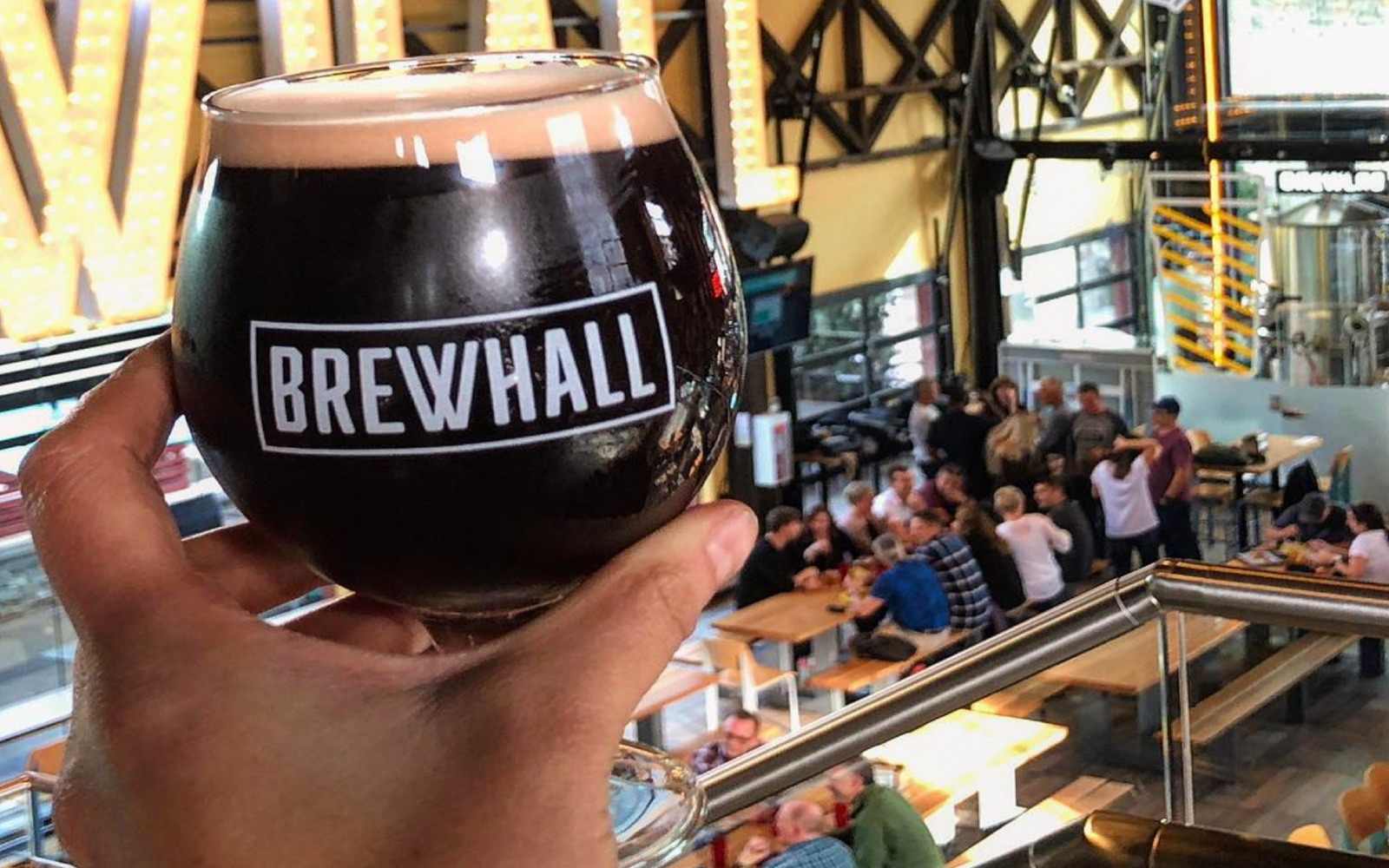 A man holds up a stout at Brewhall, Olympic Village